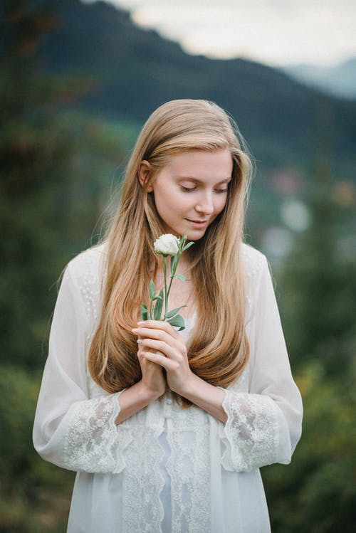 Calm young romantic female with long blond hair in white dress standing in mountainous valley with fresh flower in hand and looking down