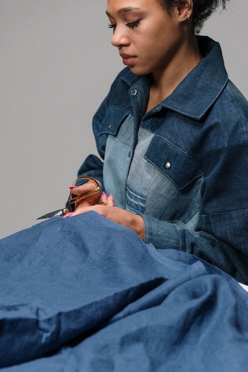 Woman in Denim Clothes Cutting Fabric