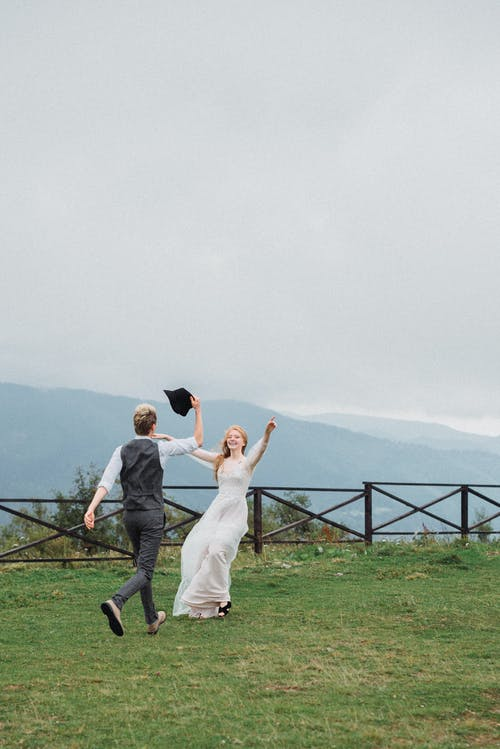 Full body of cheerful young elegant bride and groom running on grassy meadow while having fun after wedding celebration in highland under cloudy sky