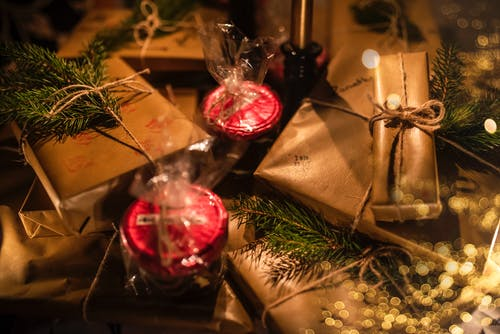 Various present boxes in wrapping paper with decorative candles and coniferous tree sprigs during New Year holiday