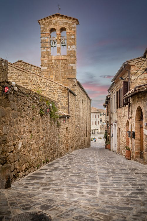 Empty cobblestone street between old house and bell tower of historic Chiesa di Sant Egidio church against cloudy sunset sky in Montalcino