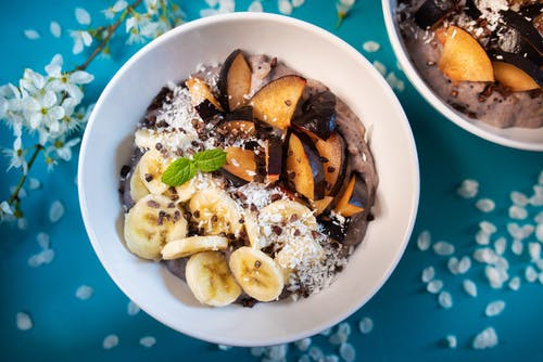 Top view of appetizing smoothie bowl topped with fresh sliced bananas and plums and decorated with coconut flakes