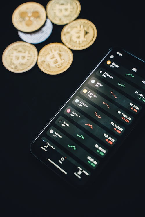 Coins scattered near smartphone with financial charts on screen