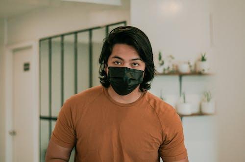 Asian man in medical mask in cafe