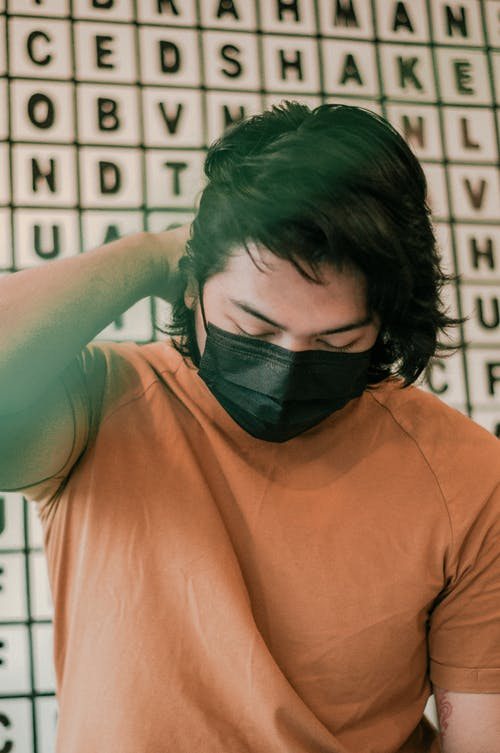 Asian man in protective mask sitting near wall in cafe