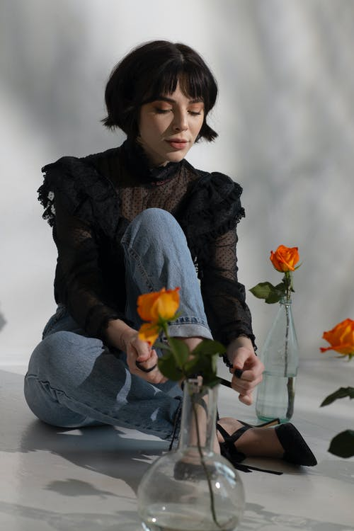 Tranquil young woman with short dark hair in stylish clothes sitting on floor surrounded by fresh roses in glass vases in light studio