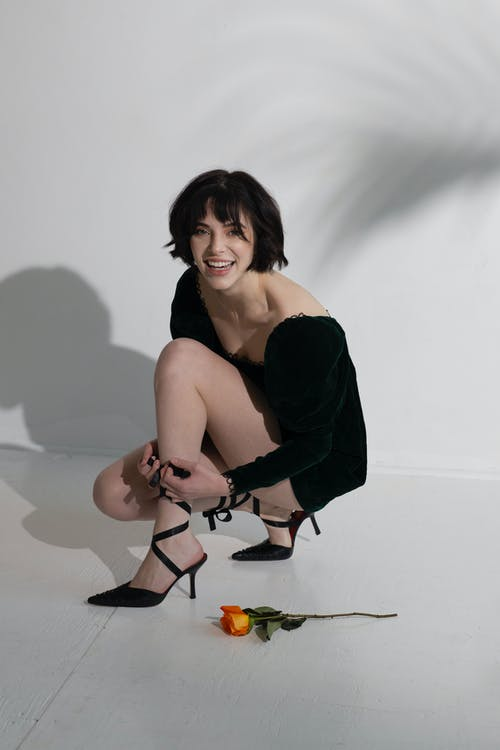 Smiling female in black dress squatting down and looking at camera