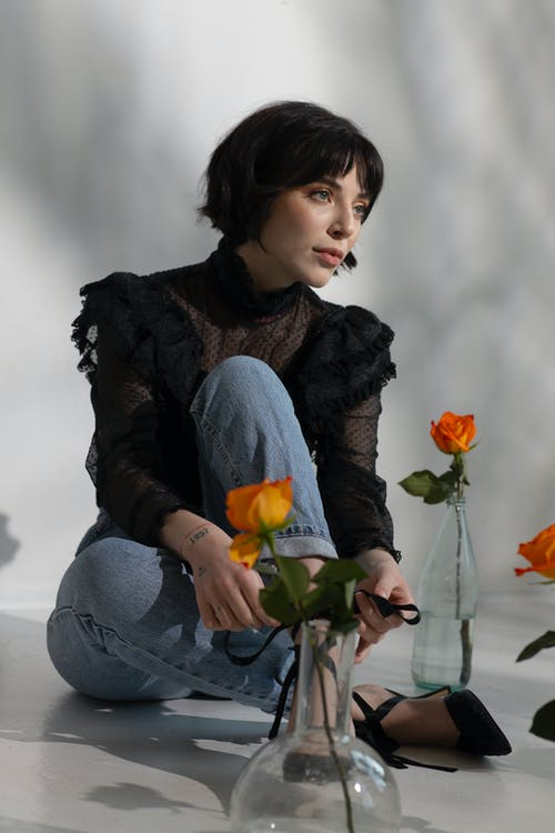 Stylish woman sitting on floor with flowers in vases