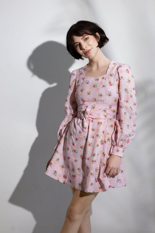 Positive woman with short brown hair in stylish dress standing against white wall and looking at camera