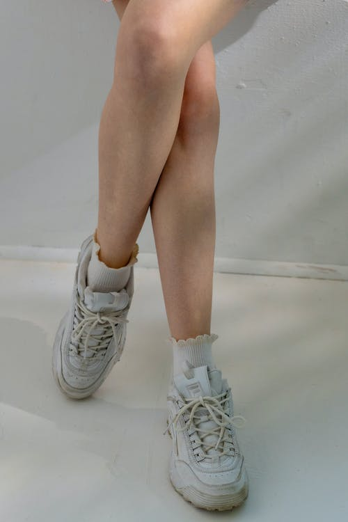 Unrecognizable woman in sneakers standing near wall