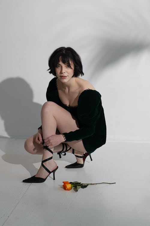 Young confident female in black dress tying high heels near orange rose on floor near white wall with shadows and looking at camera