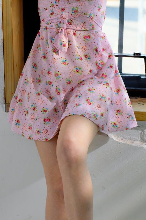 Faceless female in dress on windowsill near window