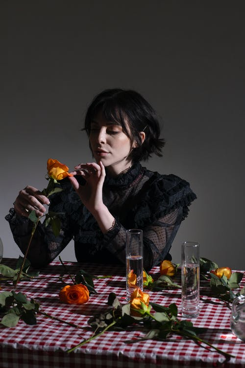 Woman in black outfit touching gentle petals of orange rose
