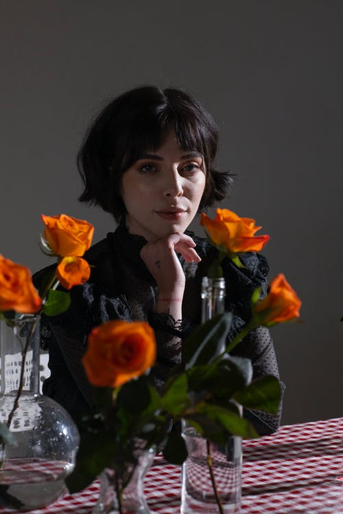 Gentle woman touching chin at table with orange delicate roses