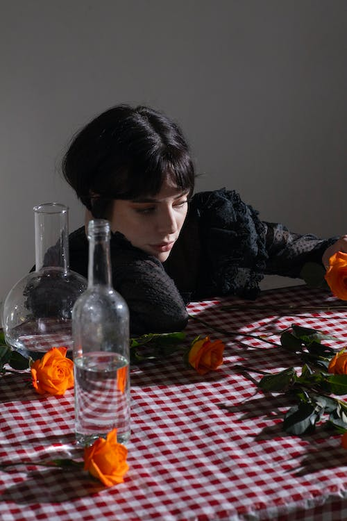 Thoughtful female with short dark hair at table with gentle roses in blossom on gray background
