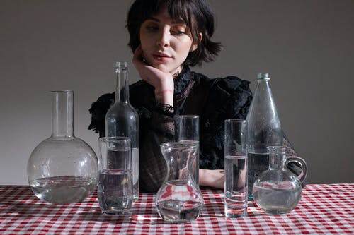 Mysterious woman at table with glassware