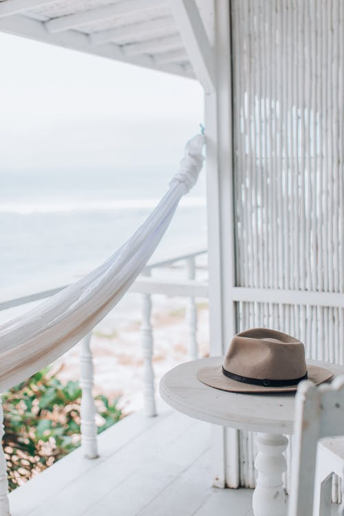 Brown Fedora Hat on White Wooden Fence