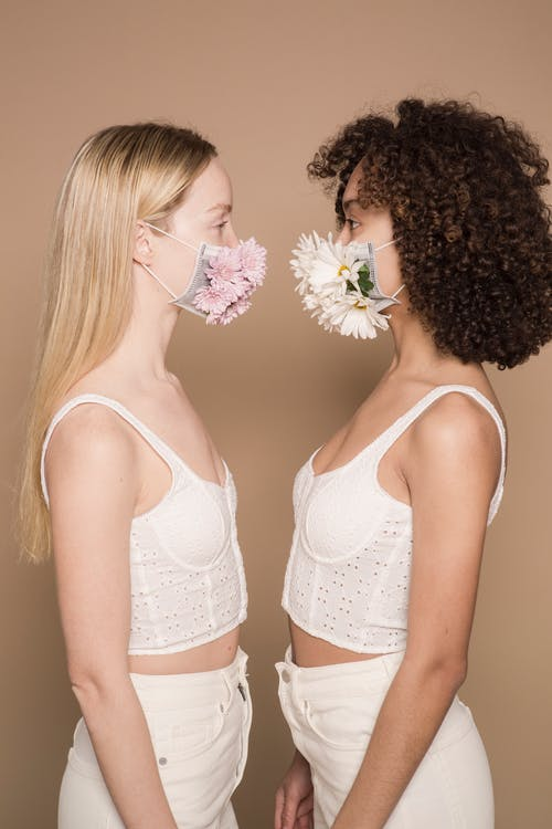 Multiracial women in flower masks in studio