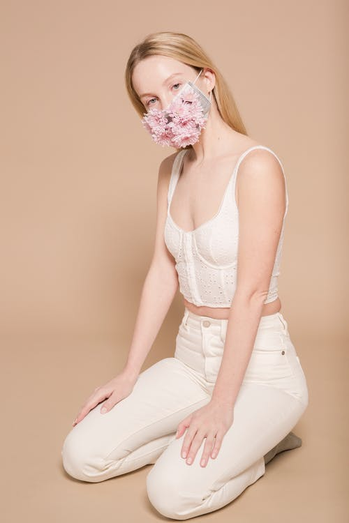 Full body of stylish female in white clothes and bright flower mask looking at camera while sitting on beige background