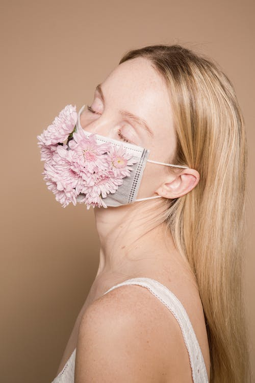Side view of peaceful female with closed eyes wearing colorful flower mask standing on beige background during disease pandemic in studio