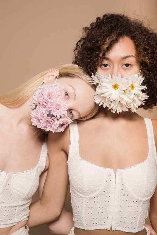 Tender diverse female friends wearing white tops and bright flower masks looking at camera against beige background during pandemic in studio