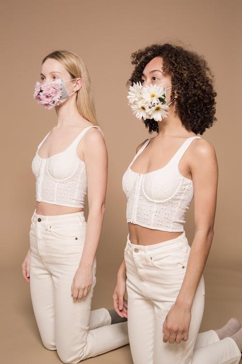 Stylish diverse women wearing flower masks
