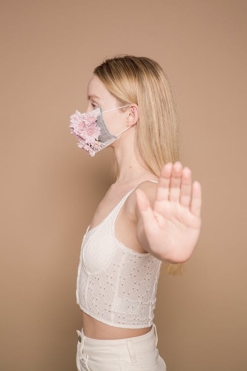 Serious woman in flower mask showing stop gesture
