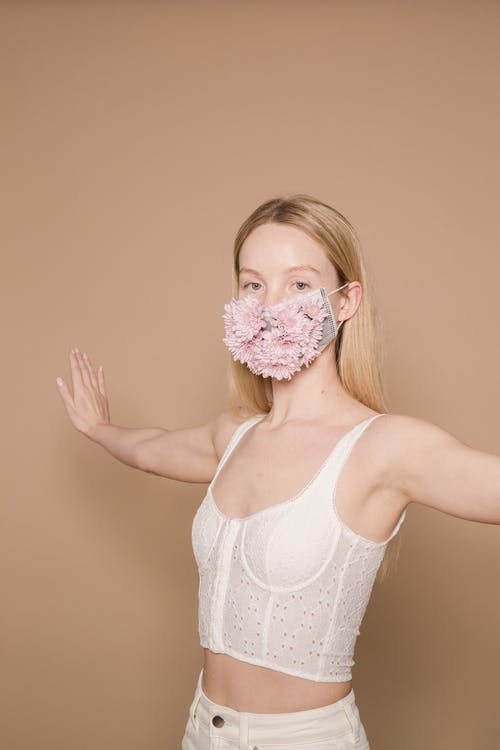 Serious female wearing white outfit and colorful flower mask looking at camera while standing against beige background with spread arms
