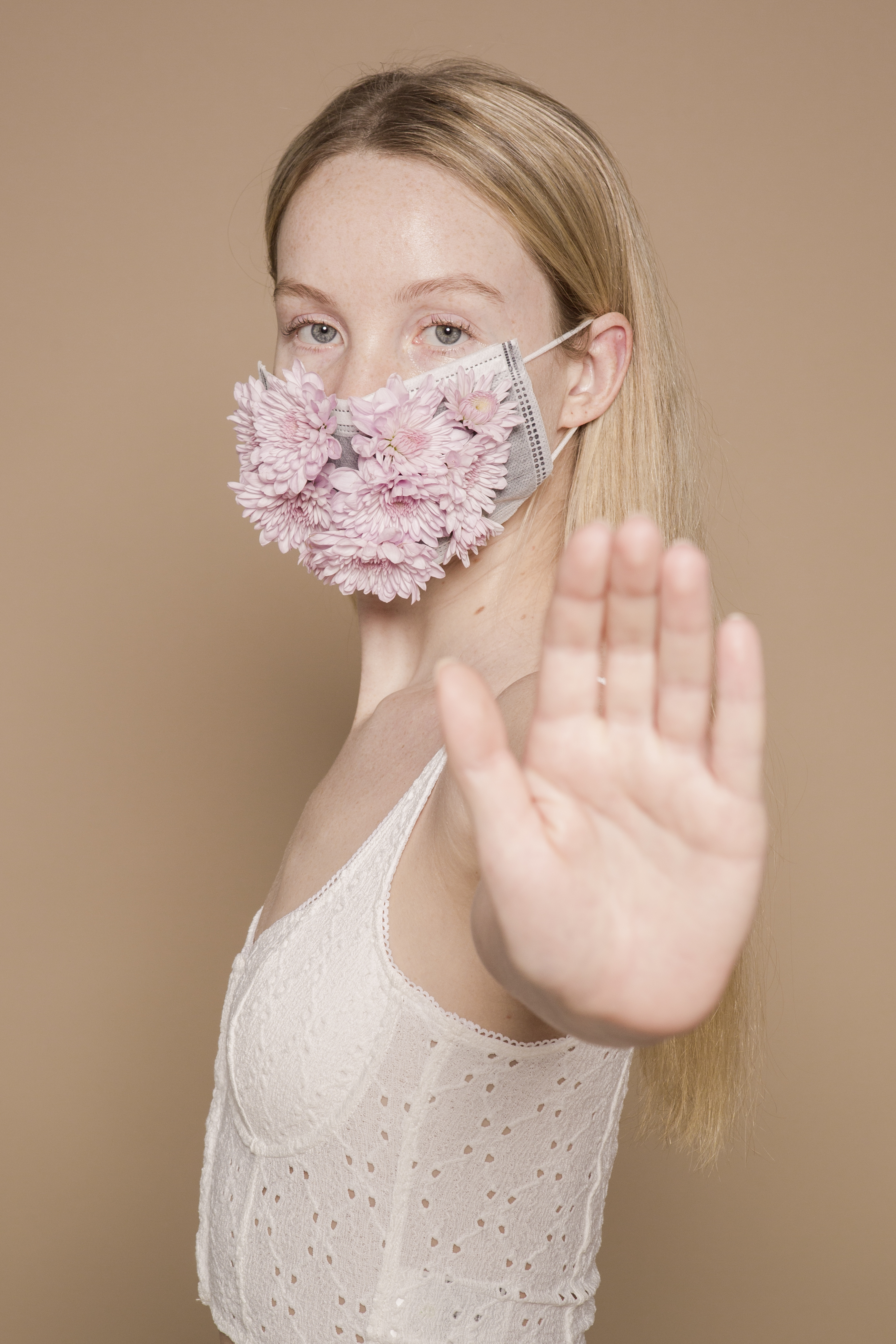 woman in flower mask showing hand to camera