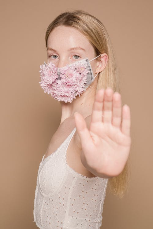Serious female wearing creative flower mask showing stop sign while standing against beige background during disease outbreak in modern studio