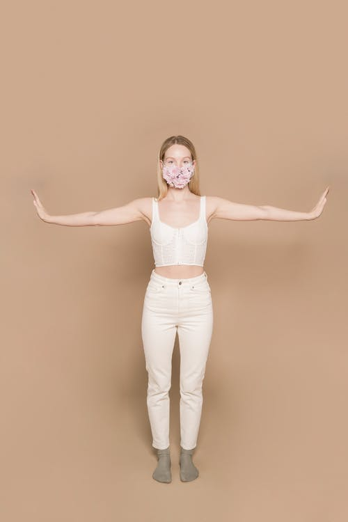 Full body of female in white outfit wearing flower mask looking at camera while standing against beige background during pandemic