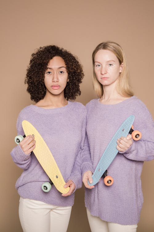 Multiethnic women with pastel colored skateboards
