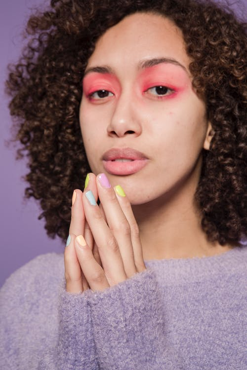 Ethnic woman with hands together and pastel manicure