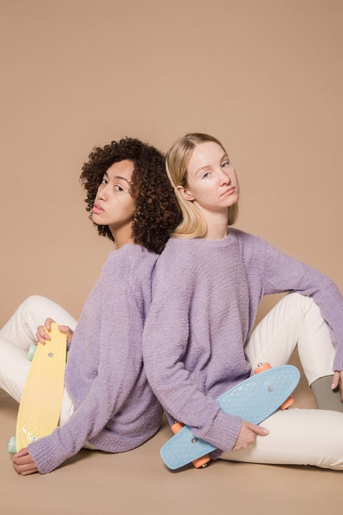 Diverse friends in purple sweater and white trousers leaning on backs and looking at camera on beige background
