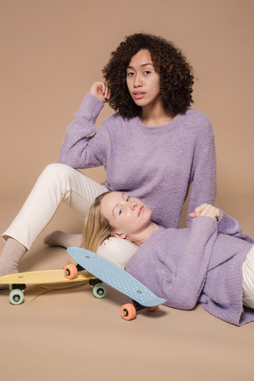 Diverse friends in casual pastel clothes relaxing and looking at camera on beige background of studio with skateboards