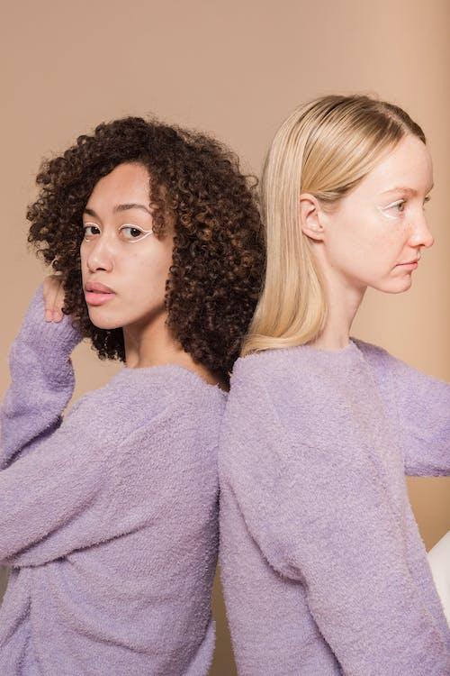 Multiracial friends leaning backs in studio