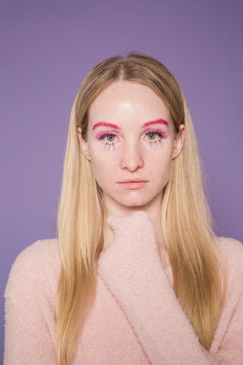 Extraordinary female with long fair hair and bright makeup looking at camera on purple background