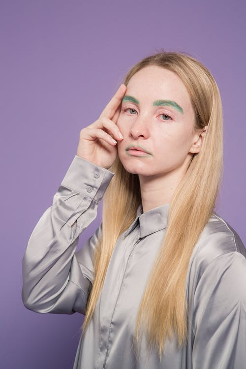 Stylish pale female with green eyebrows looking at camera on purple background of studio