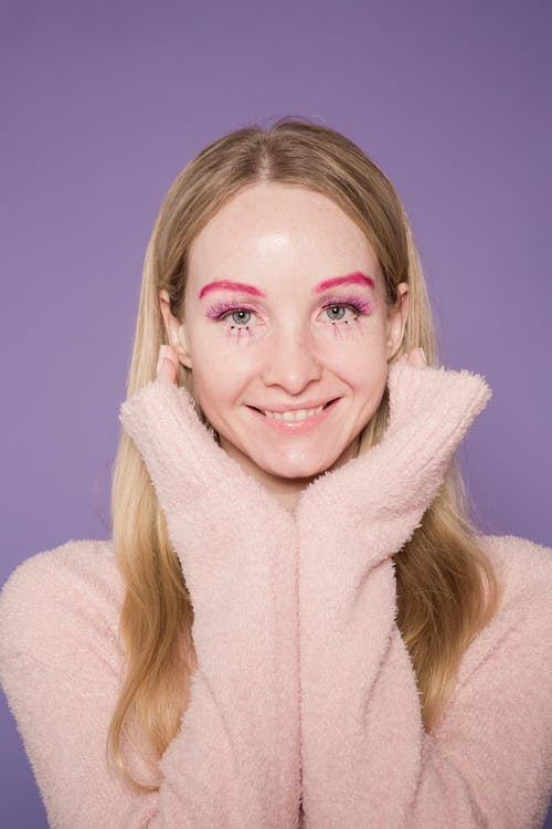 Smiling lady in colorful makeup on face in studio