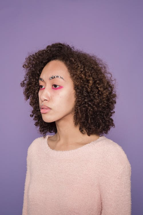 Unemotional ethnic woman with colorful makeup in studio