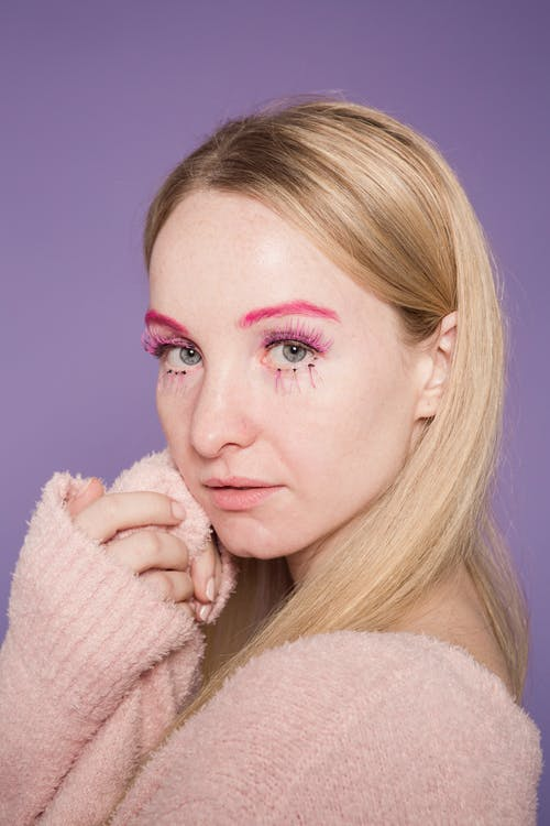 Thoughtful young female in sweater with pink colorful makeup on face looking at camera on purple background in light studio