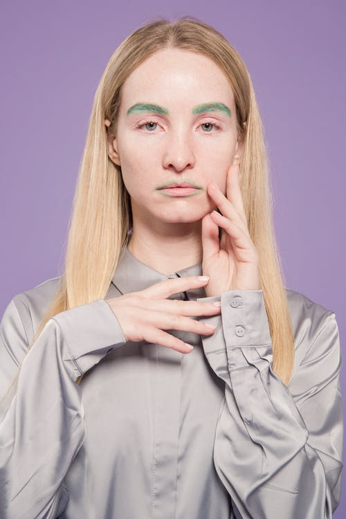Young emotionless lady in gray blouse with colorful green makeup on face looking at camera with hand on face in bright studio on violet background