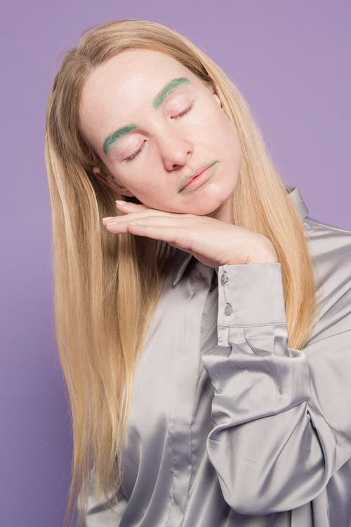Young sad lady in gray blouse with colorful green dyed eyebrows closing eyes and leaning chin on hand on violet background