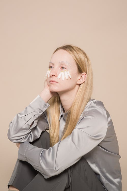 Sad young female in gray shirt with white flower petals on cheeks with hand on face looking away on beige background while sitting in light studio