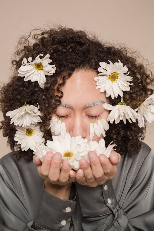 Young ethnic woman smelling fresh chamomile flowers with closed eyes