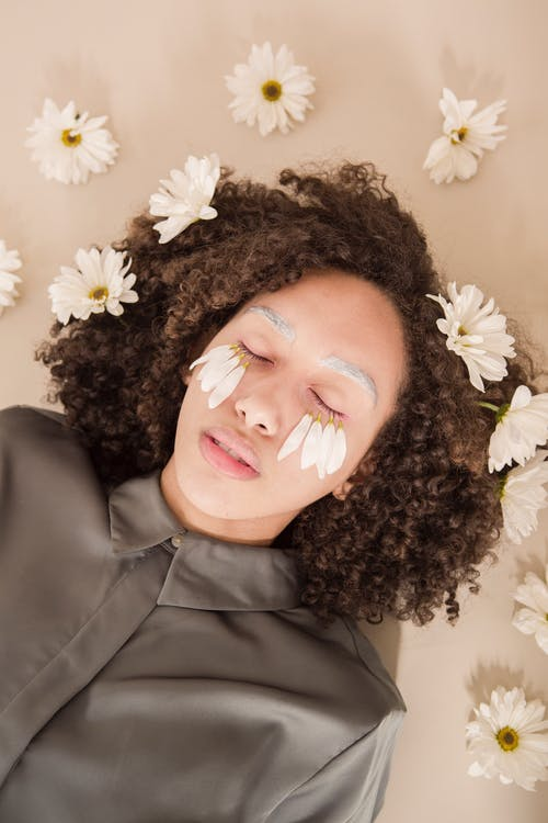 Top view of relaxed young ethnic lady with dark curly hair lying in beige surface with closed eyes and flower petals on face near scattered chamomiles