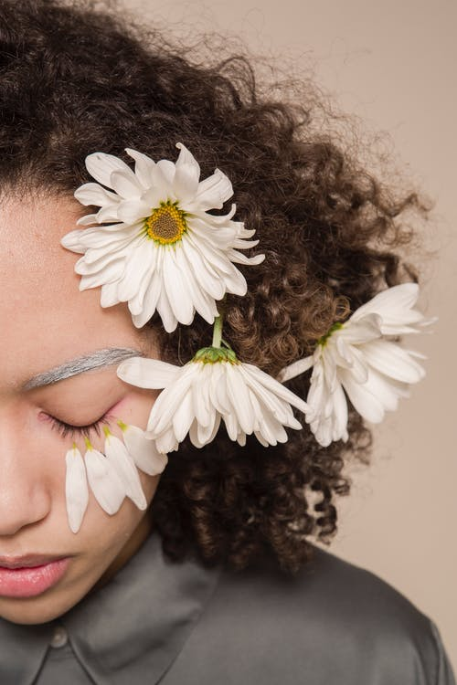 Crop sad ethnic female with eyes closed and gentle petals on face on beige background