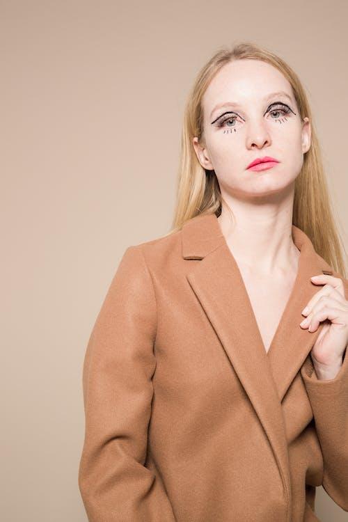 Elegant woman with extravagant makeup touching stylish beige coat