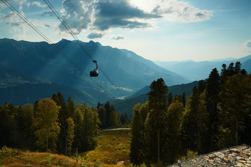 Picturesque landscape of cable car moving over scenic valley in mountains covered with green grass and high trees during sunny day under blue sky