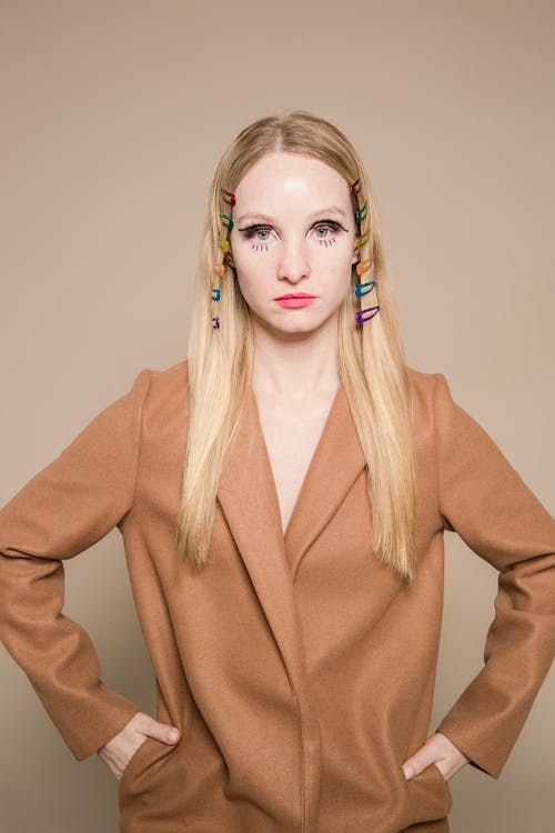 Trendy woman with hair clips on head in brown coat